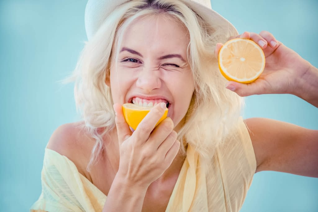 Woman biting into a lemon.